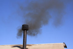 Metalldach mit dem Kamin, der schwarzen Rauch ausstößt Lizenzfreies Stockbild