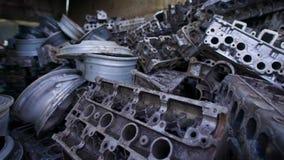 Metalldelar av gamla brutna bilar ligger i högar av restmetall i stor hangar, gamla knölar och motorer