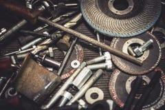 Metalldelar och hjälpmedel för auto mekaniker på en tabell Stäng sig upp sikt av fulländande utrustning, borrar, bitar, skruvar,  Royaltyfri Fotografi