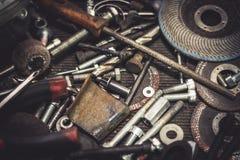 Metalldelar och hjälpmedel för auto mekaniker på en tabell Stäng sig upp sikt av fulländande utrustning, borrar, bitar, skruvar,  Arkivfoton