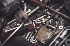 Metalldelar och hjälpmedel för auto mekaniker på en tabell Stäng sig upp sikt av fulländande utrustning, borrar, bitar, skruvar,  Fotografering för Bildbyråer