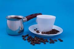 Metalldisk med bryggat kaffe bredvid ett vitt porslinkoppanseende på ett tefat royaltyfri fotografi