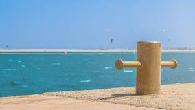 Metalldoppelpoller auf einem konkreten Pier mit blauem Wasser voll von den Drachensurfern stockfoto