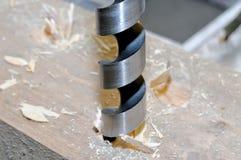 Metalldrillborren borrar ett hål i trästång arkivbild