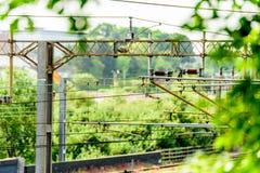 Metallelektrische HochspannungsEnergiekabel über Eisenbahn Stockfotos