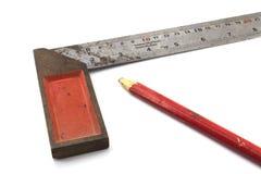 Metallen som mäter hjälpmedlet och blyertspennan på vit bakgrund Royaltyfri Foto
