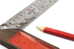 Metallen som mäter hjälpmedlet och blyertspennan på vit bakgrund Royaltyfria Foton