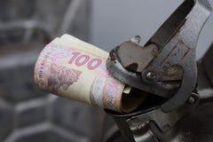 Metallfaß und ukrainisches Geld, das Konzept der Kosten des Benzins, Diesel, Gas Wieder füllen des Autos Rolle von Banknoten 100 stockbilder