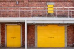 Metallgelbe Fabriktür auf Backsteinmauer Stockfoto