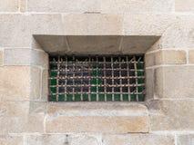 Metallgitter auf dem Fenster in der Steinwand Stockfotos