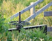 Metallhjul och staket i fält Arkivbilder