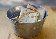 Metallic aluminum bucked with slices of bread Royalty Free Stock Photo