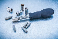 Metallic background with black screwdriver and group of steel sc Stock Photography