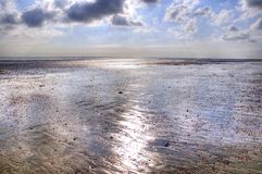 Metallic Beach. Landscape/seascape of a beach at low tide giving an almost metallic look to the wet sand Royalty Free Stock Photo