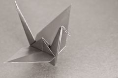 Metallic bird. An origami bird on a metallic background. Shallow depth of field. Focus on the head of the bird royalty free stock photos