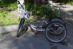 Metallic and black adult tricycle. Tricycle for adults with front and rear trunks in the yard royalty free stock photo