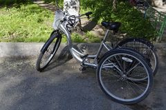 Metallic and black adult tricycle. Tricycle for adults with front and rear trunks in the yard royalty free stock image
