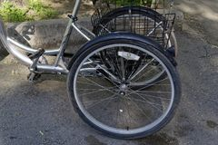 Metallic and black adult tricycle. Tricycle for adults with front and rear trunks in the yard stock images