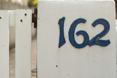 Metallic blue house numbers on white picke Stock Photos