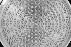 Metallic bottom of the cooking pan. Closeup round silver shiny d. Metallic bottom of the cooking pan. Closeup of a surface representing round silver shiny royalty free stock photography