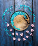 Metallic bowl with sea salt, scoop and flowers on blue wooden table, wellness background, top view Royalty Free Stock Images