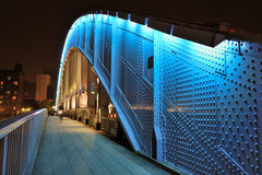 Metallic bridge. Pedestrian way along the metallic arc structure of Eitai bridge with moving bicycle by night time in Tokyo Japan; focus on metallic structure Stock Images