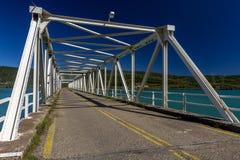 Metallic bridge over an artificial lake. Royalty Free Stock Image