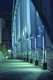 Metallic bridge vertical. Pedestrian way along the metallic arc structure of city bridge illuminated by night Royalty Free Stock Photography