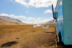 Metallic caravan of nomads between the mountaines. Metallic caravan of nomads and wet laundry on a rope in the middle of a mountain plateau in Central Asia Royalty Free Stock Photography