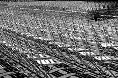 Metallic chairs. Multitude of metallic chair aligned in the sun for a concert Vienna Austria Royalty Free Stock Images