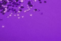 Metallic confetti on festive ultra violet background. royalty free stock images