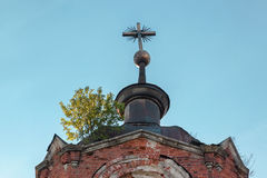 Metallic cross with a Masonic symbol on the dome of an abandoned temple Stock Image