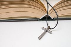 Metallic crucifix and opened Holy Bible Royalty Free Stock Photography