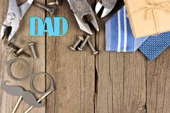 Metallic DAD sign with top corner border on wood. Metallic DAD sign with top corner border of gifts, tools, and ties on a wooden background Stock Image