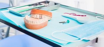 Metallic dentist tools with acrylic denture .False teeth.close up on a dentist chair in Dentist Clinic .blue tone Royalty Free Stock Photo