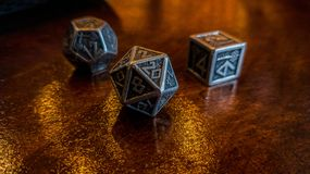 Metallic Dice On a Wood Table in Low Light royalty free stock photos