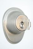 Metallic door lock with a key. Close-up of metallic door lock with a key in the keyhole. Focus on the keyhole Stock Photo