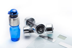 Metallic dumbbells, scales and sport bottle isolated on white. drink water. Equipment sport and healthy living concept royalty free stock photos