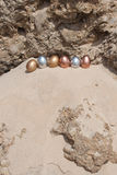 Metallic Easter Eggs on a cliff. Six Metallic Easter Eggs lined up on a little rock cliff Royalty Free Stock Photos