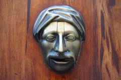 Metallic face at an old door, Valencia. Metallic face at an old door Stock Photo
