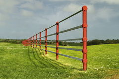 Metallic fence in a green field. Metallic fence in Irish countryside, with green grass, blue sky and sunshine Royalty Free Stock Photography