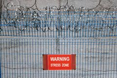 Metallic fence with red warning sign Stress zone. Stock Photo