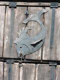 Metallic fish on wooden door Stock Photos