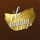 Metallic foil shining calligraphy Be Happy poster. Vector Gold Print Paint Stain Design on Wood Background Royalty Free Stock Images
