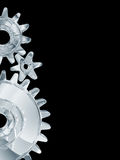 Metallic Gears Background. An illustrated background with a design formed by Chrome metallic gears / cogs, isolated on black background Royalty Free Stock Photography
