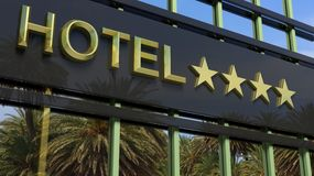 Metallic glass hotel sign board with four golden stars Royalty Free Stock Photo