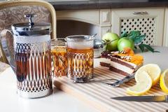 Metallic glasses holders, press, tea, cake, kitchen interior details Stock Photography
