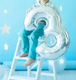 Metallic glossy silver balloon in the form of a number 3 in the hands of a boy who sits on a white staircase royalty free stock photos