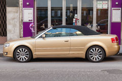 Metallic gold Audi A4 Cabriolet stands on city street Stock Photos