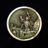 Pewter button `Trumpeter of Krakow` against black background. Metallic grey, round, and large, the sewing notion displays a story book icon of Poland and Polish Stock Image